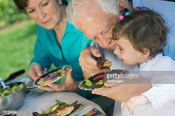 Senior man feeding chicken to his granddaughter with a senior woman sitting beside them