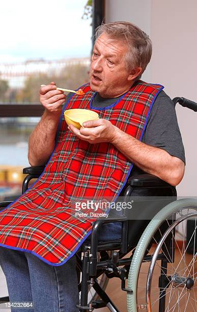 Senior man feeding himself in wheelchair