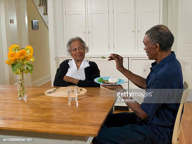 Senior man feeding wife with vegetables in kitchen