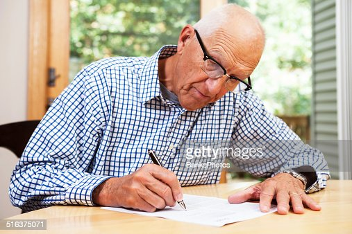 Senior Man Filling Out Paperwork, Signing Document