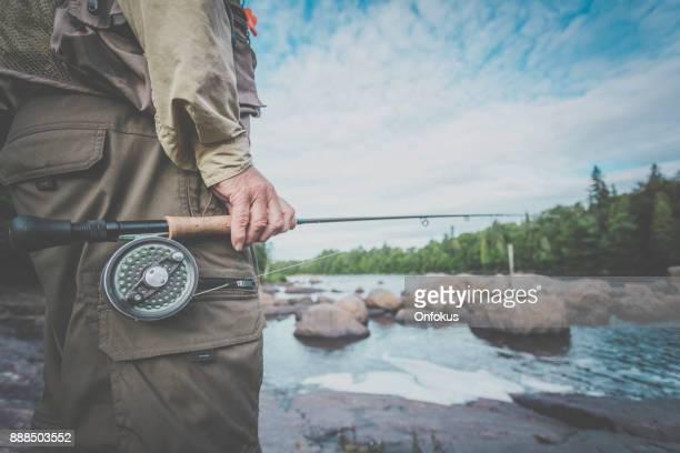 Senior Man Fisherman Fly Fishing in A River