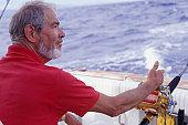 Senior man fishing from yacht
