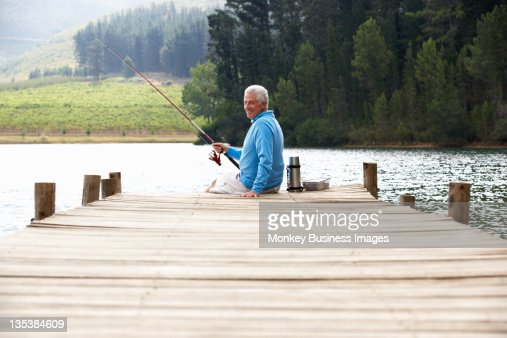 Senior man fishing on jetty : Stock Photo