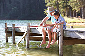 Senior man sitting on jetty fishing in lake with grandson