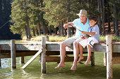Senior man fishing with grandson sitting on jetty