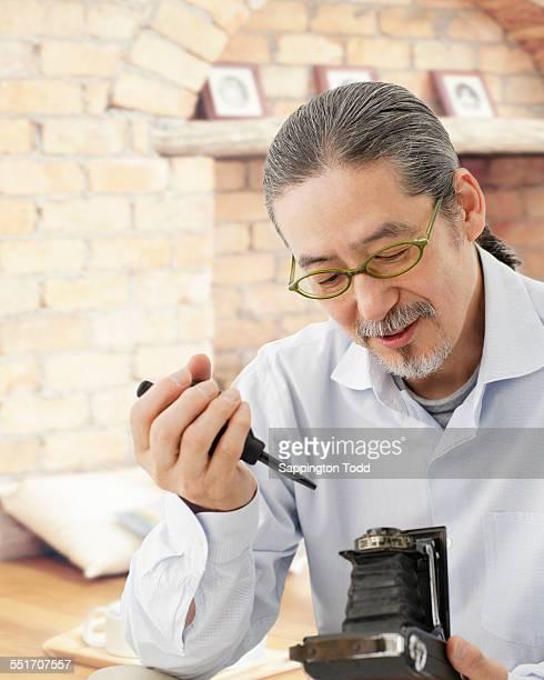 Senior Man Fixing His Old Camera