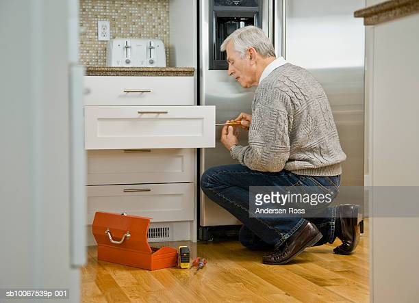 Senior man fixing kitchen drawer, side view