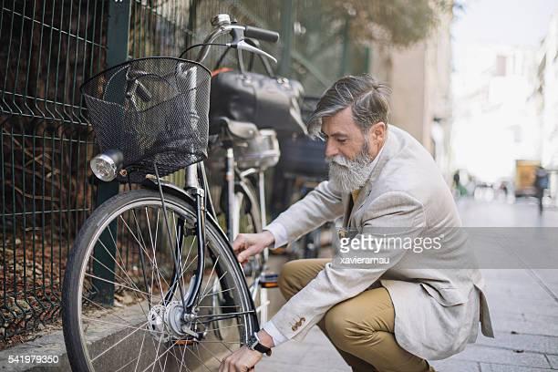 Senior man fixing tyre on his bicycle at Paris