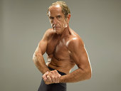 Senior man flexing bicep, portrait