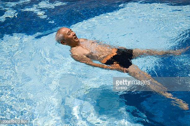 Senior man floating on back in swimming pool, elevated view