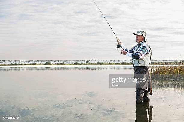 Senior man fly fishing