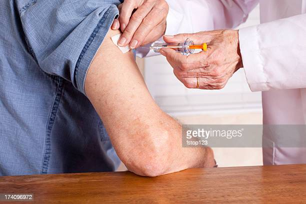 Senior man getting an injection from a nurse or doctor