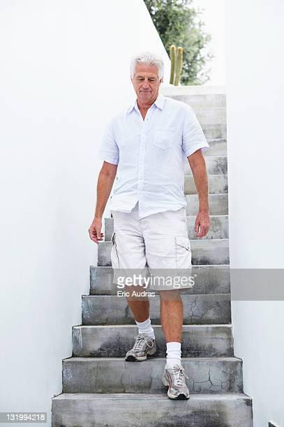 Senior man getting down steps