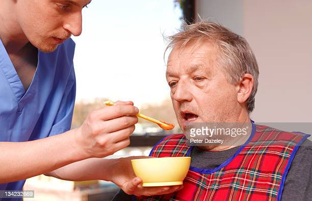 Senior man getting fed by carer in care home
