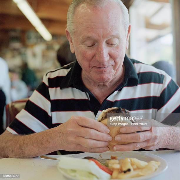 A senior man getting ready to eat a hamburger