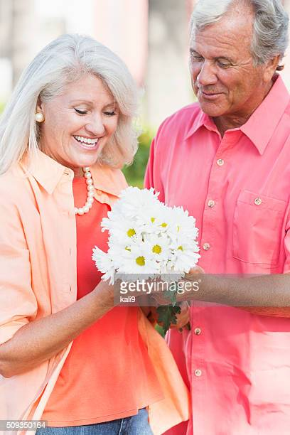 Senior man giving wife a bouquet of flowers