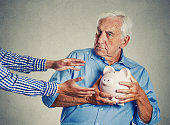 Closeup portrait senior man grandfather holding piggy bank looking suspicious trying to protect his savings from being stolen isolated on gray wall background. Financial fraud concept 'n