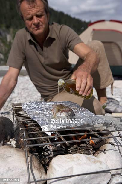 Senior Man Grilling Fish Over Campfire