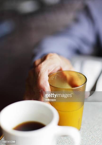 年配の男性手を持つオレンジジュース