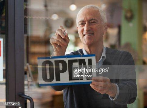 Senior man hanging open sign