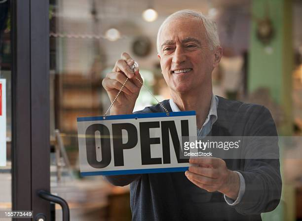 Senior man hanging open sign