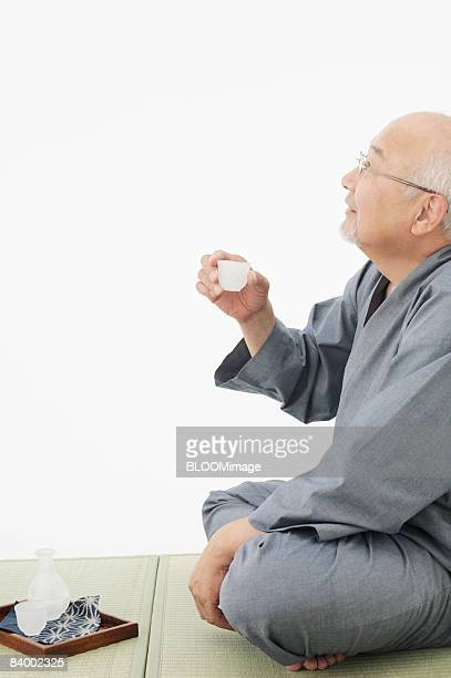 Senior man having sake, studio shot
