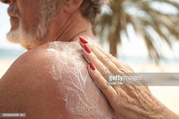 Senior man having sun cream rubbed on back by senior woman, close-up