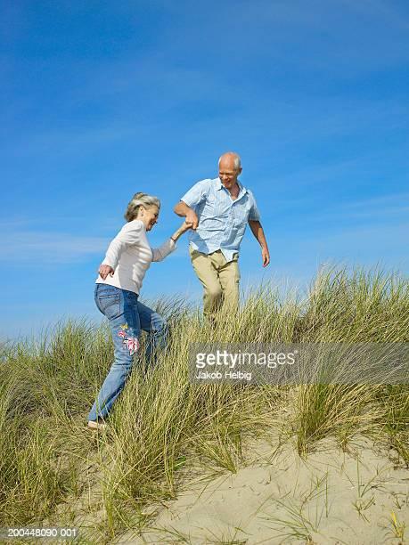 Senior man helping senior woman climb up sand dune, smiling