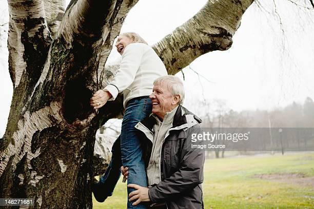 Senior man helping woman climb tree in park