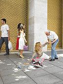 Senior man helping woman fallen on street