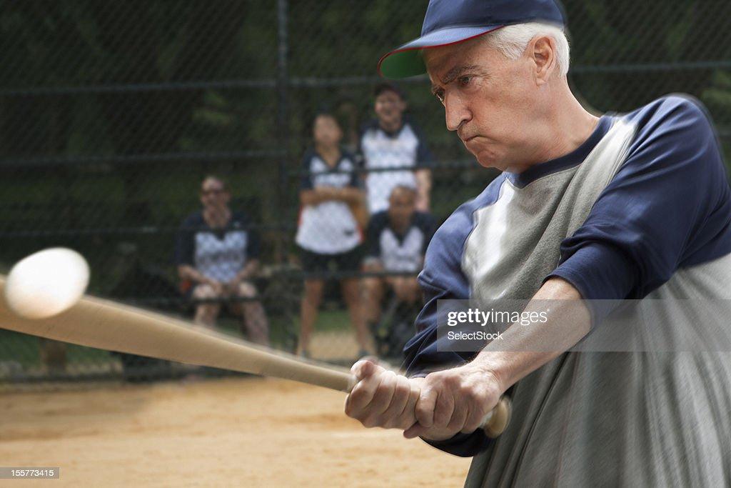 Senior man hitting baseball with bat