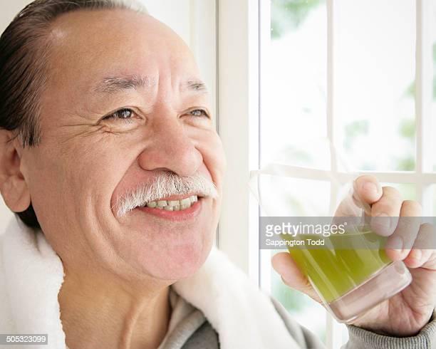 Senior Man Holding A Glass Of Juice