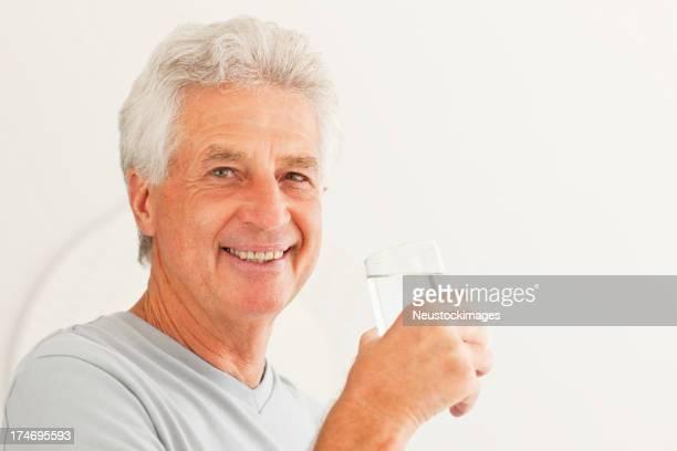 Senior uomo che tiene un bicchiere di acqua
