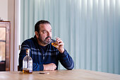senior man looking out the window indoors holding a glass of whiskey with the bottle beside him