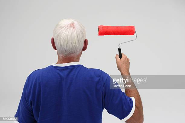 Senior man holding a paint roller, rear view