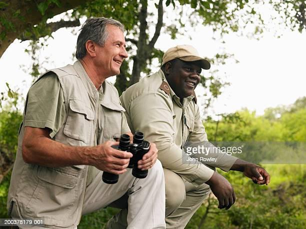 Senior homme tenant jumelles, au safari avec guide, souriant
