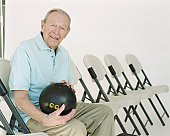 Senior man holding bowling ball, smiling, portrait