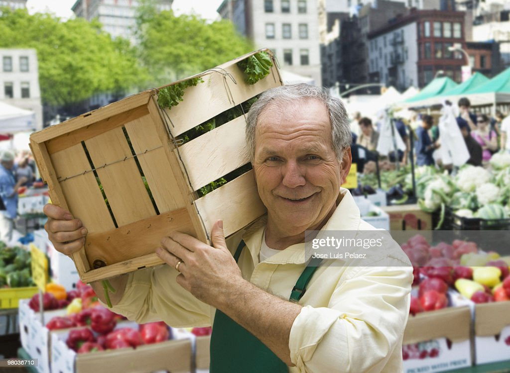 Senior man holding box of produce : Stock Photo