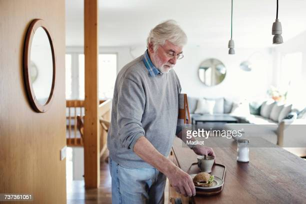 Senior man holding breakfast in tray at home