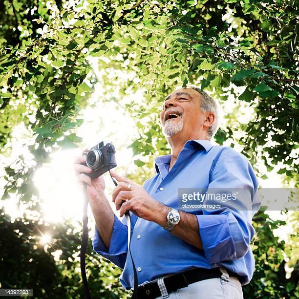 Senior hombre que agarra cámara
