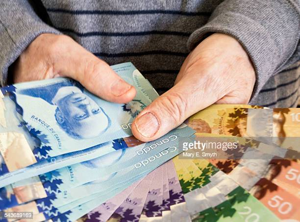 Senior Man Holding Canadian Paper Currency
