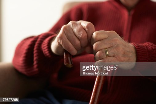 Senior man holding cane, mid section, close-up of hands