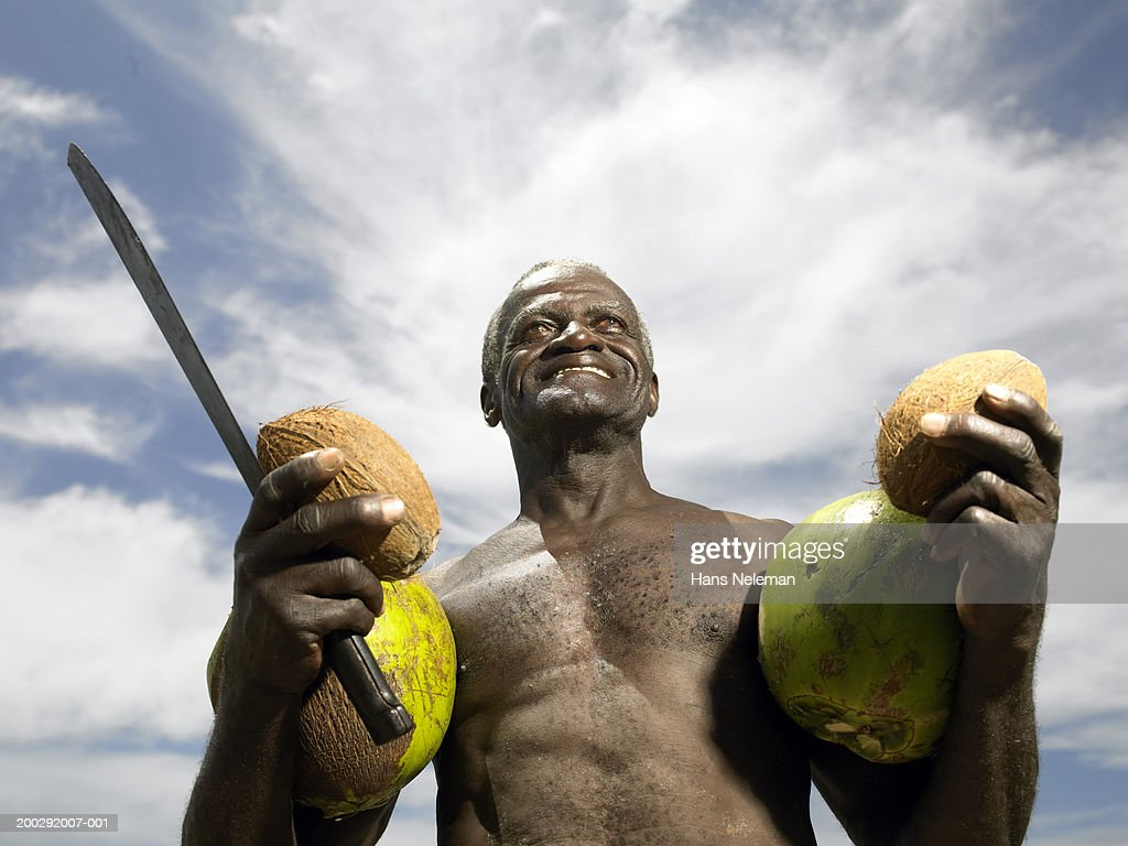 Senior man holding coconuts on beach, smiling, low angle view : Stock Photo