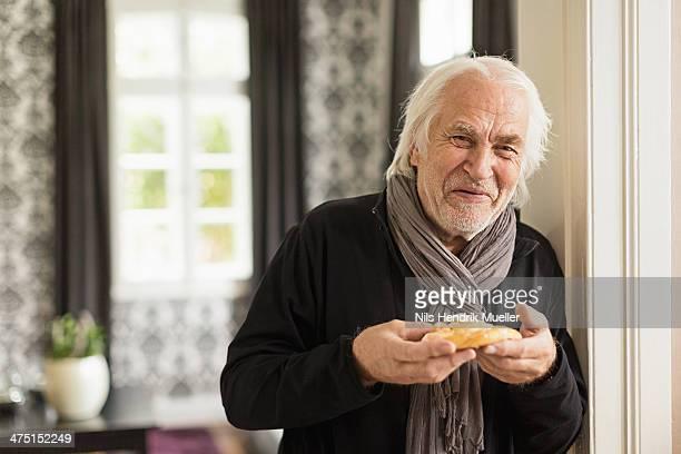 Senior man holding danish pastry