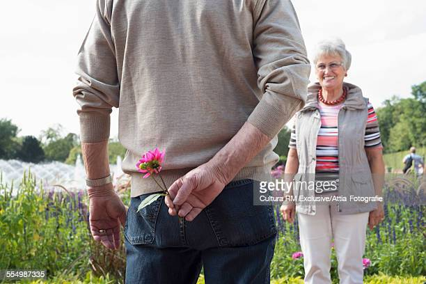 Senior man holding flower behind his back for wife in park