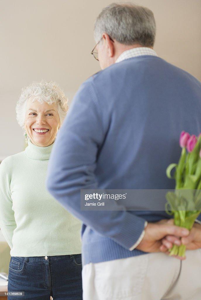 Senior man holding flowers behind back : Stock Photo