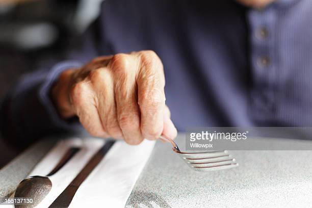 Senior Man Holding Fork at Restaurant Table
