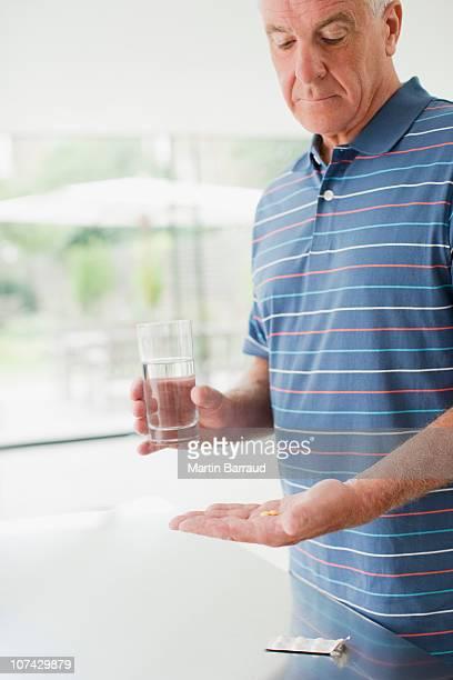 Idoso a segurar copo de água e Comprimido