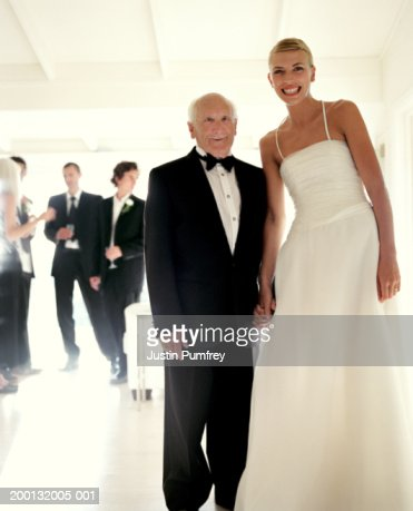 Senior man holding hands with young bride, portrait