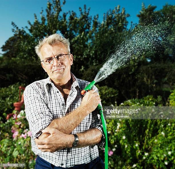 Senior man holding hose in garden, smiling, portrait